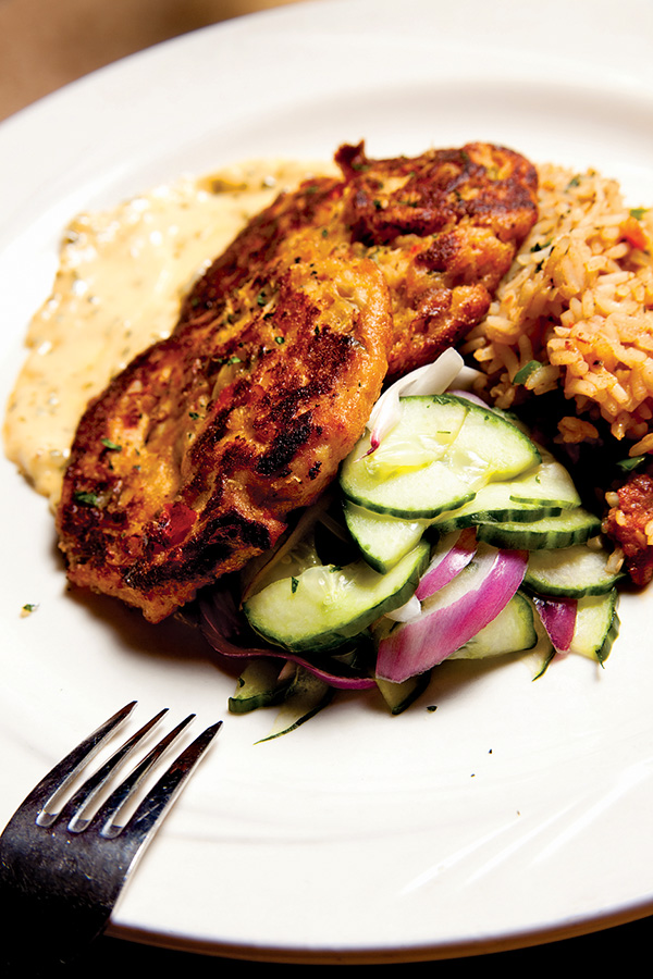 Maryland crab cakes, made of broiled jumbo lump Atlantic crab and served with cucumber salad and rice.